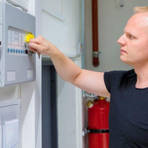 it-engineer-opening-fire-panel-in-server-room-PV6MT7Y
